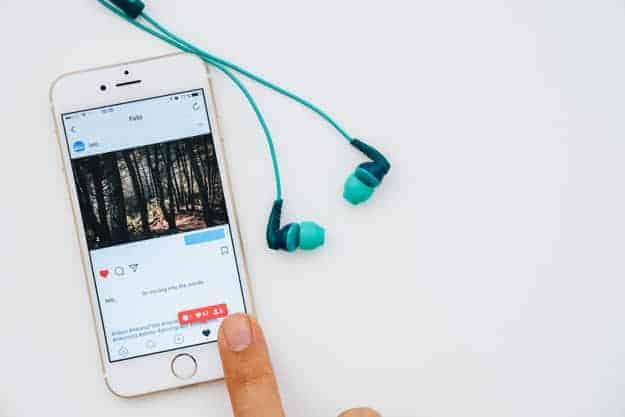 auriculares-y-dedo-tocando-el-movil-con-instagram